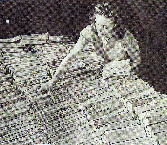 A file clerk at the FBI working with a table covered with files. (Photo by Thomas D. Mcavoy
